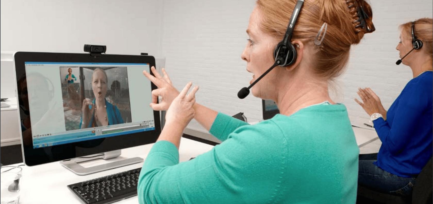 Gebarentolken van KPN Teletolk helpen een beller met een telefoongesprek.
