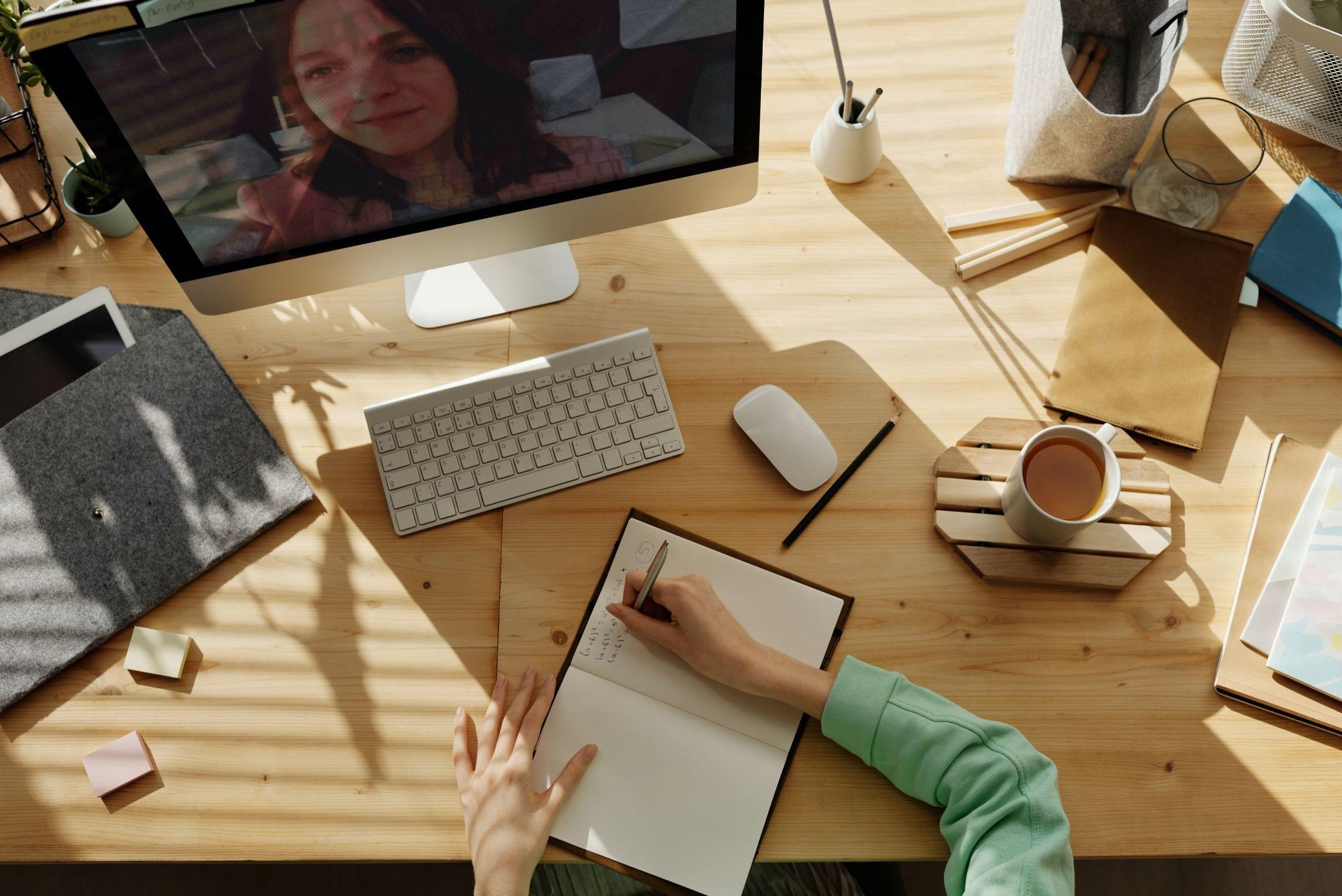 Afbeelding van een bureau waarop een scherm te zien is met iemand die aan het videobellen is