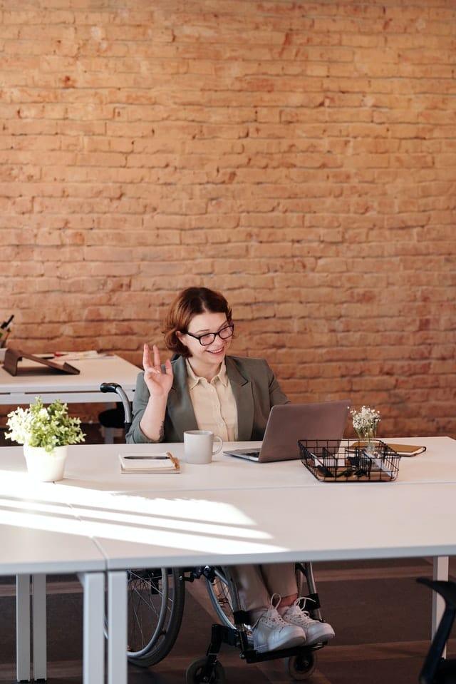 Vrouw in rolstoel zwaait naar het scherm op haar laptop.