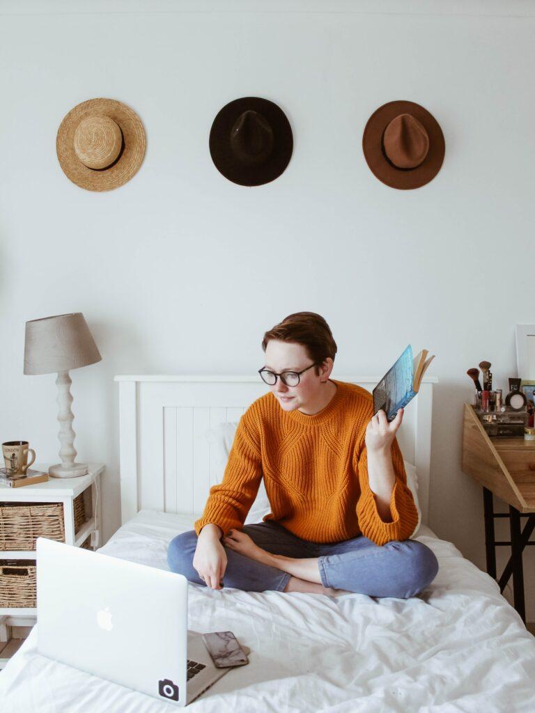student zit op bed met laptop